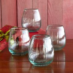 "Handblown of subtly green recycled glass, these generously curved wine tumblers celebrate the season in an eco-friendly way. Made in Colombia. Dishwasher safe. Set of 4. 8 oz., 5-3/4""H."