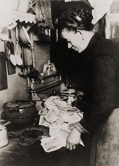 German women burning money to fuel her stove during the post World War I hyper-inflation in 1923. At the time, an American dollar was worth 800 million German marks.