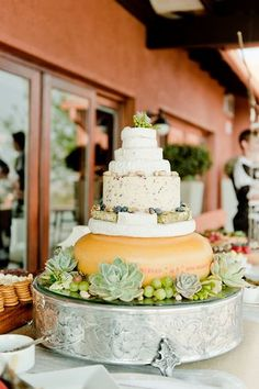 Cheese Wedding Cake: A grand wedding cake created from tiers of cheese wheels decorated with succulents and fruits.