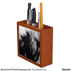 "The Black Fire IV Desk Organizer designed by Artist C.L. Brown features fire photography converted to black and white. Keep your desk neat and tidy with a unique, artist-designed desk organizer. Great for keeping clutter contained! Organizer is made of wood with a mahogany finish and is printed front and back on two 4.25"" white ceramic tiles. Designed with three compartments and dimensions of 5"" l x 5"" w x 1.75"" d."