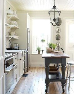 ,Cottage kitchen. White with wood floor.  Check out the island.