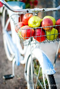 A cruiser bike with apples in the basket. I love this shot and would love to ride that bike.
