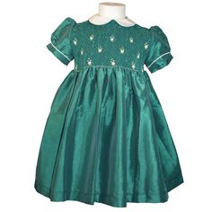 """Scarlet (Jade) - Traditional smocked dress with embroidery overlay.  Styled with short sleeves and """"Peter Pan"""" collar. Button cuffs to sleeves. Button fastening at the back, with matching fabric """"ribbons"""" to tie a bow.  Fabric piping to collar and cuffs to compliment embroidery. Available in sizes 6 months - 8 years."""