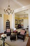 Living room with corner cabinet, built in bookshelves, leather chairs, pink striped pillows