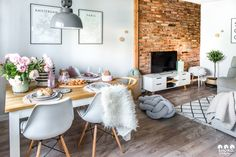 Sala de jantar estilo escandinavo, mesa de madeira cadeira eames, parede de tijolinhos e luminária industrial cinza.