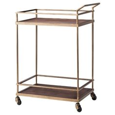 • Brass metal for strength and durability<br>• 2 wooden trays for display<br>• Wheels at bottom for pushing around with handle<br><br>Get ready for your next big gathering with the Wood & Brass Finish Bar Cart – Threshold. You'll enjoy serving your guests their drinks to order with this modern mixed material bar cart.