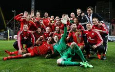 The Wales players celebrate on the pitch after the final whistle as they booked their plac...