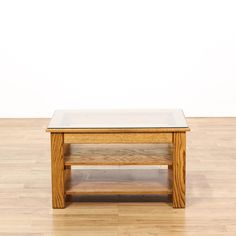 This coffee table is featured in a solid oak wood with a glossy finish. This traditional style cocktail table has a glass top, 2 bottom tier shelves, and sturdy legs. Perfect for storing magazines and coffee table books! #americantraditional #tables #coffeetable #sandiegovintage #vintagefurniture