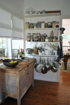 Cabinet in front of kitchen windows, shelves with storage jars, etc, pots hanging from the bottom shelf.