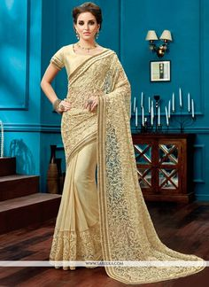 Make the heads turn whenever you costume up in such a stunning cream net designer saree.. The lace work seems chic and great for any party. Comes with matching blouse. (Slight variation in color, fabr...