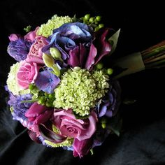 Rich bouquet of violet, purple, and green for a fresh look.  Hypericum adds texture.
