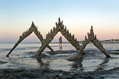 Using driftwood and bits of line found on the beach, an artist creates out-of-this-world sand castles.