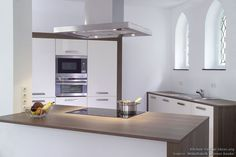 This minimalist kitchen with cream cabinets and walnut wood neatly complements the white walls and Gothic arches of this historic house in Germany. Kitchen Cabinet Design, Kitchen Cabinets, Cupboards, Houses In Germany, Kitchen Pictures, Kitchen Ideas, Minimalist Kitchen, Cool Kitchens, Modern Kitchens