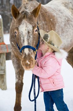 Little blonde girl kissing big Appaloosa horse outdoors in snow,.