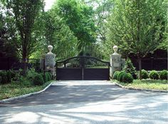 A classic farmhouse style driveway gate has an updated look with black paint and stone round statues on stone posts. This gate was designed to match with the new ranch-style fencing. Driveway entry gate designed and installed by Tri State Gate in Bedford Hills, New York.