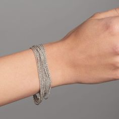 This shimmering double-length bracelet is made up of 8 rhodanized silver strands that wrap around your wrist for luxourious effect. It is a stunning addition to any outfit, adding a touch of contemporary glamour.