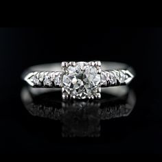 A traditional style engagement ring from the 1950's. This perfect vintage platinum ring features a .93 carat European cut diamond set with claw prongs and highlighted by three small accent diamonds set down the shoulder terminating in a knife edge shank.
