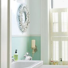 Make an all-white bath with lofty ceilings like this one feel cozy by painting a soothing color under a chair rail.