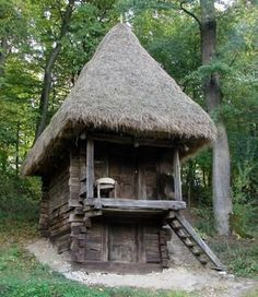 Two storey wooden cabin with thatch roof.