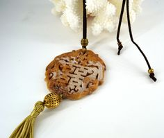 Round Jade necklace with suede cord and bronze metal beads. Jade carved with oriental motives and handmade tassel.
