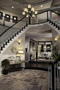 Duplo escadas em arco descendente para baixo o hall de entrada rodada criando um caminho de entrada de dois andares.  Andar é telha cinza.  Foyer leva até um pouso na sala de jantar.  #HomeStratosphere Por Jo monte da