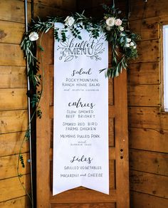 Wedding buffet menu sign - hand lettered calligraphy paper scroll on vintage door with floral garland