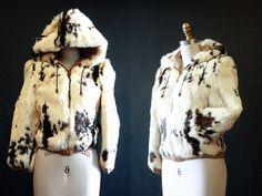 Jahrgang 1970 Kaninchenpelz & Leder beschnitten Bomberjacke mit Kapuze  INFORMATIONEN: • Kaninchenpelz und Leder • Reißverschluss vorne • gesteppte Futter • zugeschnittene Passform • Kapuze mit Kordelzug • Hüfttaschen  CA.: 1970  GRÖßE: klein passt über einen 2-4 kleine Schulter: 14 Büste: 34 Taille: 30 Ärmel: 16 Länge: 21  Farbe: schwarz, weiß, braun  Stoff: Kaninchen, Leder  Zustand: große! Kaninchenfell in einem unglaublichen Zustand. Toten-Lager mit Originaletiketten hängen.