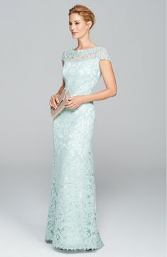 Lavish corded lace adds a hint of regal opulence to this illusion-yoke gown.Whilst the flattering cap sleeves and column cut creates the most stunning silhouette just perfect for the big day. Also available in a navy/nude colour. With a back zip closure. Lined. Summer Mother Of The Bride Dresses, Mother Of Bride Outfits, Mother Of The Bride Gown, Mother Of Groom Dresses, Mothers Dresses, Mother Bride, Green Lace Dresses, Blue Wedding Dresses, Gown Wedding