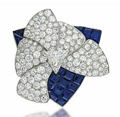 AN ART DECO SAPPHIRE AND DIAMOND BROOCH  Of asymmetrical design, the stylised flowerhead with triangular-cut diamond centre and surrounding pavé-set brilliant-cut diamond petals, to the calibre sapphire triangular surround, late 1930s, 3.6cm wide