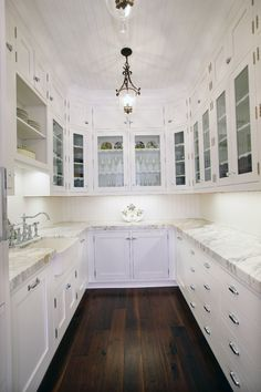 Love the dark wood floor and contrasting white everything else/ White painted cabinets.