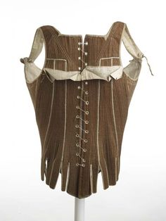 """1780-1795 Stays. """"Corset of brown cotton twill with shoulder straps that tie at front with cotton (linen?) twill tape; holes down centre back for closure.""""  Museum of London."""