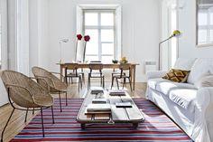 Una caja blanca se vistió con muebles de madera natural, un sofá blanco, sillones de rattan y una mesa ratona baja que genera poco volumen en el espacio.  /Archivo LIVING