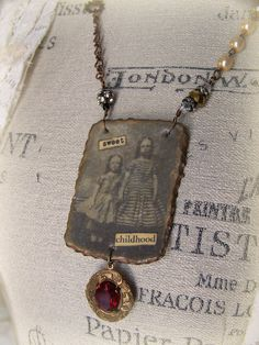 Several antique elements have gone into the assembly of this one of a kind necklace. Rich patina, sparkly rhinestones, antique image, rosary beads,