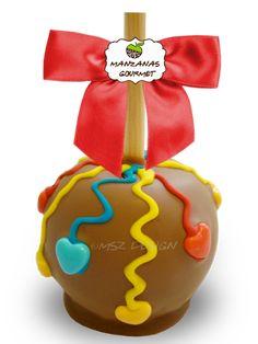 Manzana envuelta de caramelo con capa de chocolate de leche, rociada con tiras de chocolate color rojo, azul y amarillo, decorada con corazones de azúcar.