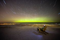 "On February 19 night-sky fan and Michigan resident Shawn Malone pulled out a seat to capture this unusual view of the auroral display with stars wheeling across the sky.    ""Here the northern lights glow over the frozen shore of Lake Superior,"" he wrote in an email to National Geographic News about his 17-minute-long exposure."