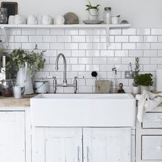 white subway tile + open shelf + apron sink + wood countertop