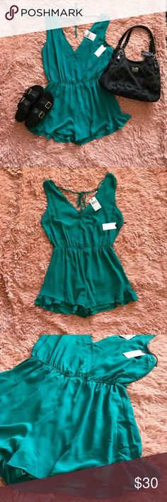 """NWT ASTR Cadmium/Teal Sleeveless Romper NWT ASTR cadmium/teal sleeveless romper in size medium. Gentle pleats flutter the surplice bodice and leg-flaunting shorts of a sporty sleeveless romper with a nipped-in waist for a flattering, figure-defining silhouette. • 31"""" length; 2 1/2"""" inseam; 32"""" leg opening • Back tie closure • Sheer, but lined • 100% polyester ASTR Other"""