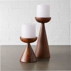 Shop baltic pillar candle holders.   Dark wood and luxe copper combine to create a sculptural footing for the glow of a single pillar candle.  Hand-turned shesham wood is topped with a cap of copper reflecting warm light and a modern sensibility.