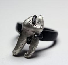 Blood Milk Jewels - It is set into a hand carved ring base, cast immortal in oxidized sterling silver whose prongs hold a small cast sterling bear tooth.