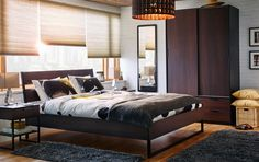 A dark brown double bed frame in a brown, gray and white bedroom.