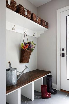 Light gray classic East Coast Hamptons-style small  mudroom paint color is Benjamin Moore HC-170 Stonington Gray -- love how the soft dove gray paint looks with the white trim and blackened bronze hardware on the door, white scalloped bracket open shelves with dark wicker baskets on top, hanging flower basket, and built-in storage bench with cubbies and dark mahogany butcher block seat, with dark gray rectangular slate floor tiles and white grout.