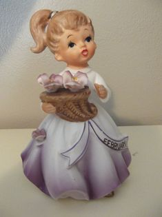 This is a very nice vintage Miss February girl figurine. She is holding a basket of purple ceramic flowers and there is one on her dress also.. She is in excellent condition with no chips cracks or breaks, and her paint is excellent. February is written in gold paint, and there is a gold band around her ponytail. Very pretty. This figurine is 5 1/2 inches tall. I combine shipping on multiple items. Perfect for display with your Shabby Chic Decor