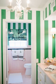 Stripes done right in a preppy, tropical bathroom