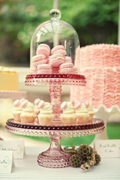 Pink macarons on a pink cake plate, cupcakes with a pop of pink, and a fabulously ruffled pink cake