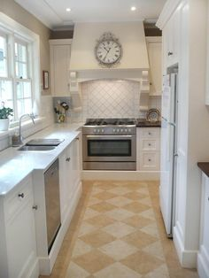 This French-country kitchen shown on HGTV's inspiration gallery features placement of the range along the back wall, making for an interesting and efficient layout. The ornate hood over the range makes this the focal point of the kitchen.