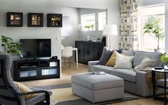 Black TV bench, wall cabinets and free-standing cabinets in a white, yellow and grey livingroom.