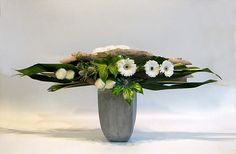 Horizontal flower arrangement - Phormium tenax variegata, Aspidistra leaves and pieces of Eucalyptus bark pinned into position horizontally - Fatshedera lizei foliage,  Arum italicum marmoratum, white Gerberas and white Carnations with some silver grey Eryngiums and white sisal spheres ~ by Chrissie Harten - Design 330