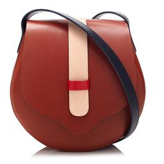 Brandy Body, Navy Handle, Panna Loop, Red Loophole.  Go hands-free with the TINCT Cross Body. It's hardware free and wonderfully light, with a small zipped interior pocket and leather loop fastening. A chic over the shoulder bag that comes in six different colours.  Made in the UK using Italian vegetable tanned leather, each bag is presented in a box for storing, and comes with a dust bag.  Dimensions W - 23cm H - 22.5cm Depth - 7cm    Interior pocket W - 11cm H - 15cm    Handle Drop - 48cm…