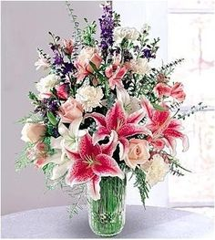 Stargazer lilies and pink roses, aswirl with purple larkspur and pink alstroemeria, are gracefully arranged in an elegant vase. Description from 2flowers.com. I searched for this on bing.com/images