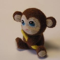 sweet felted toy monkey holding a banana.